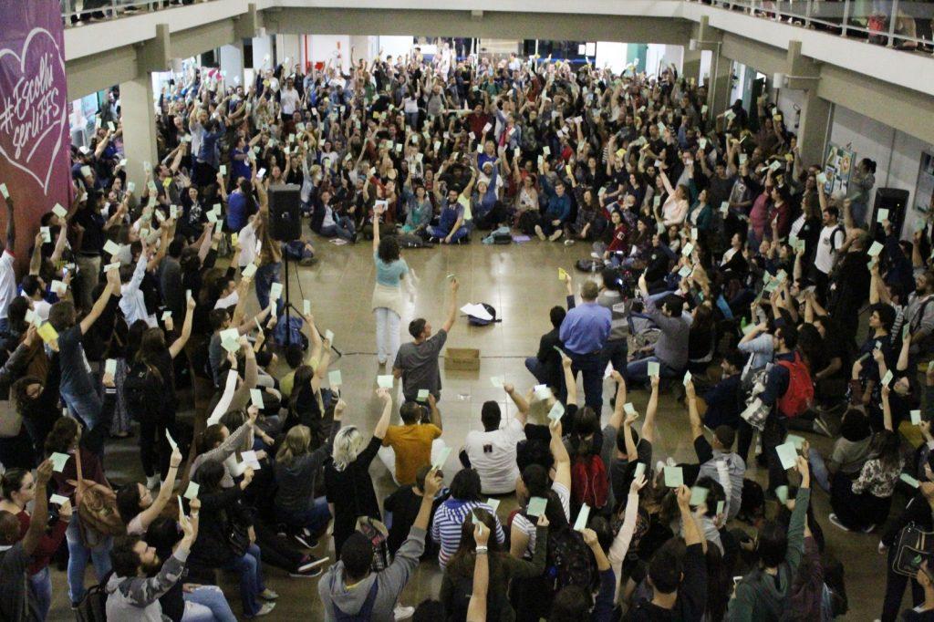 Estudantes levantam suas fichas de votação para aprovarem proposta de destituição do novo reitor nomeado da UFFS, Marcelo Recktenvald.